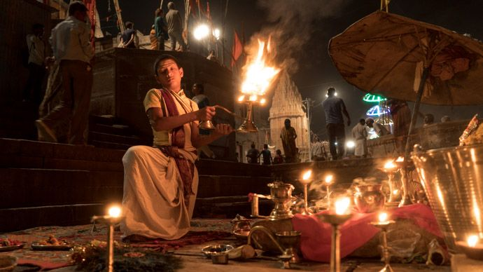 A young priest with candle lights in India